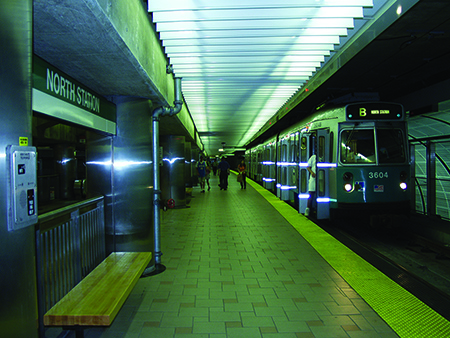 A B Line Green Line train sits on the tracks at North Station. Several people stand on the platform.