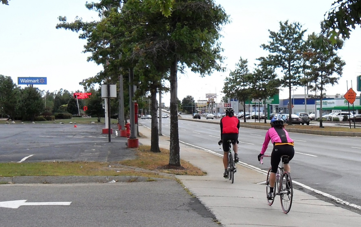 Photo of bicyclists riding on sidewalk next to three traffic lanes