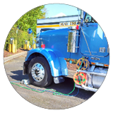 A blue semi truck is hooked up to a charging station.